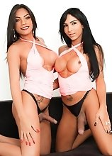Busty T-girls Yasmim Dornelles and Jane Costa look sensational in matching pink outfits. Their big boners bulge from their panties as they passionatel